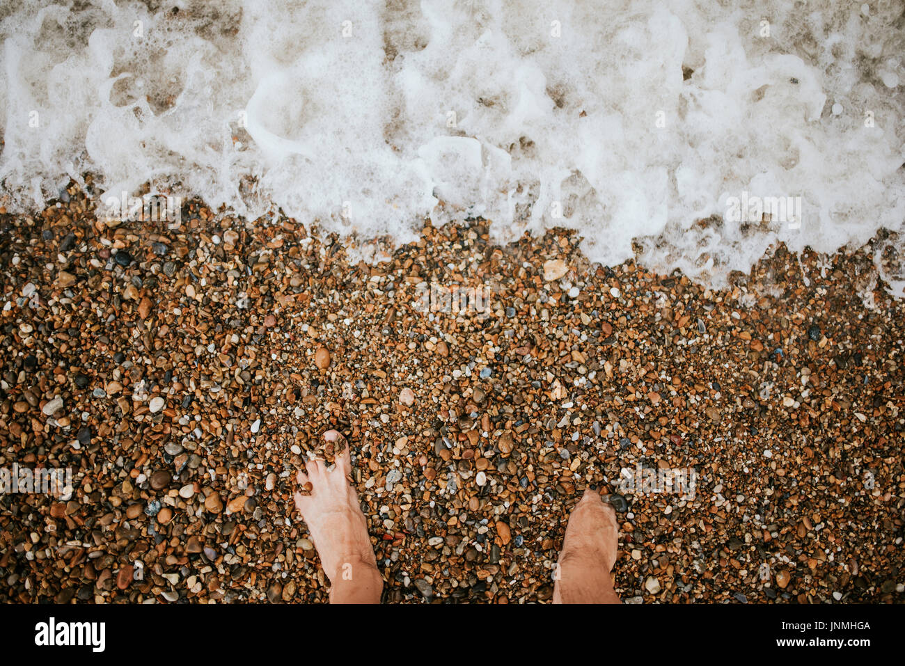 Top view of man bare feet on the bach - Stock Image