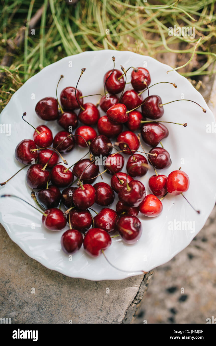 Group od delicious fresh cherries on white plate - Stock Image