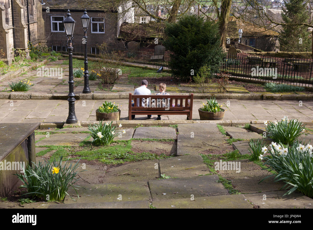 Couple sitting on bench in the churchyard, Haworth, West Yorkshire - Stock Image