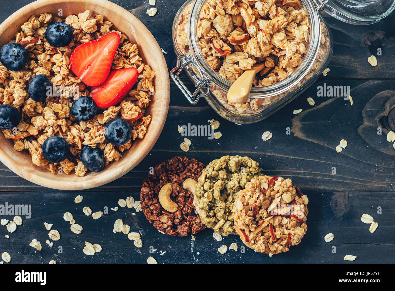 Homemade granola and fresh berries on wood table with space. - Stock Image
