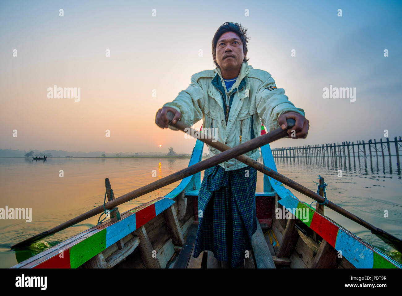 Amarapura, Mandalay region, Myanmar. Man rowing on his colorful boat  on the Taungthaman lake  at sunrise, with - Stock Image