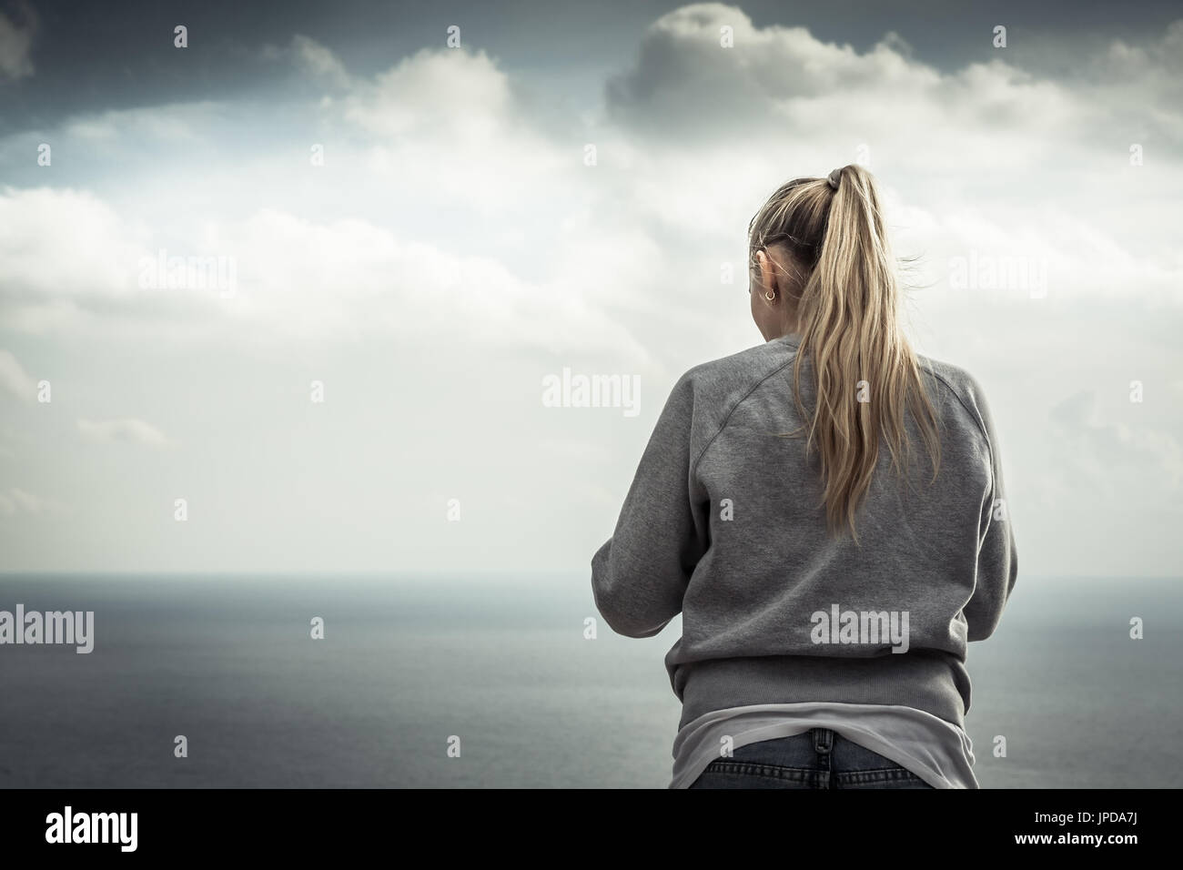 Young blonde smiling woman portrait with with blurred mountains landscape on background in overcast day - Stock Image