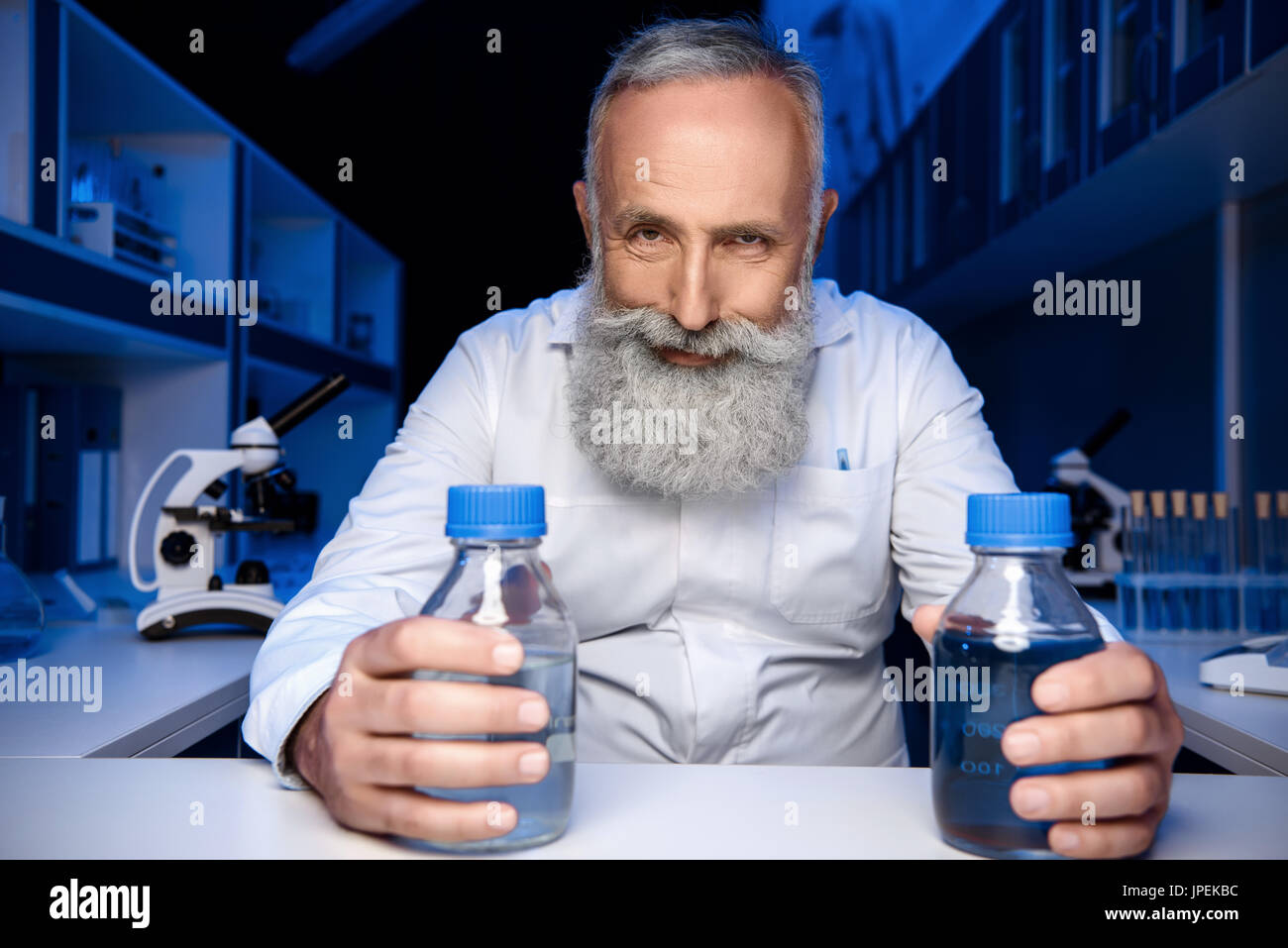 portrait of cunning scientist holding bottles with reagents and looking at camera in laboratory - Stock Image