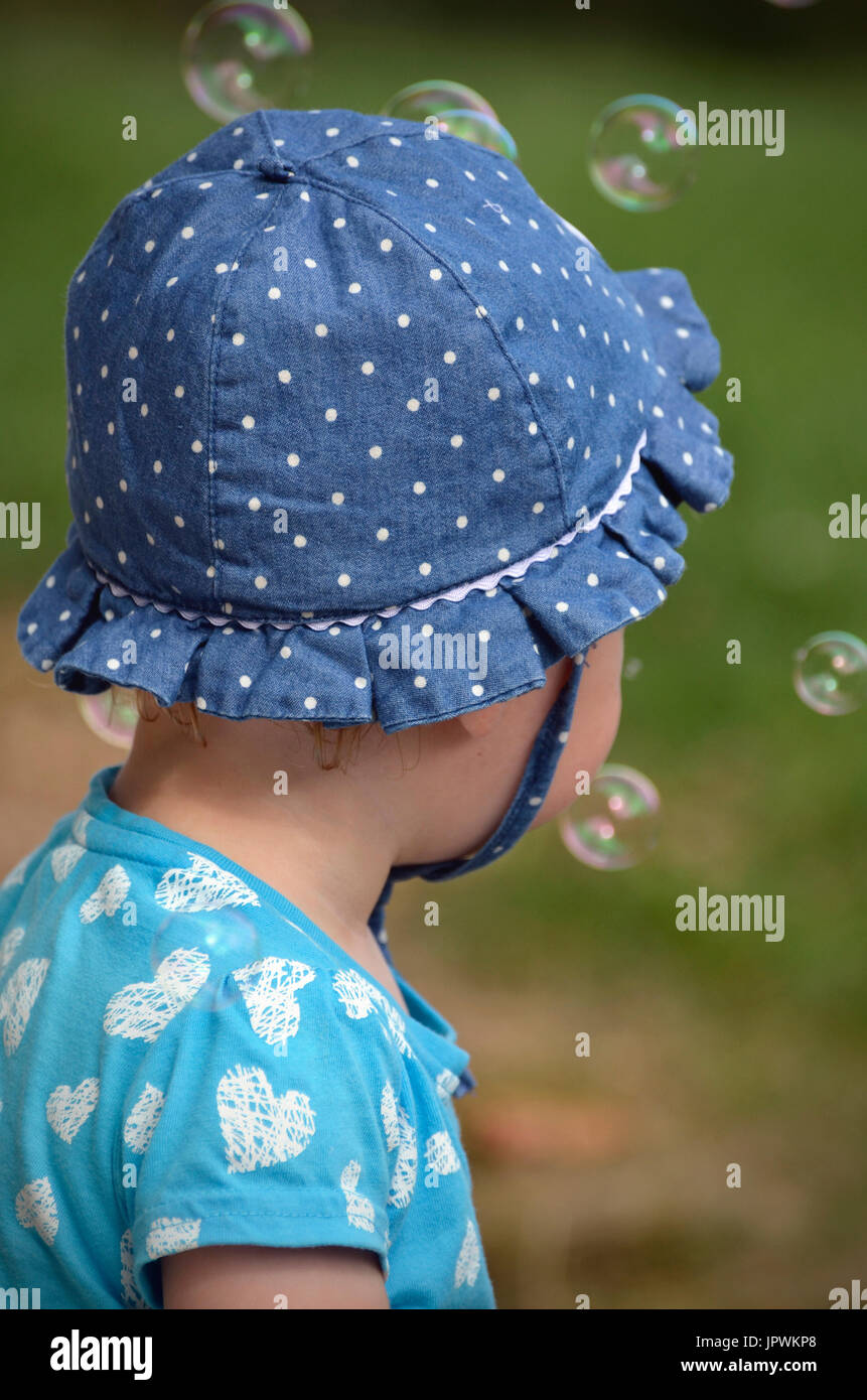 child with bubbles from behind - Stock Image