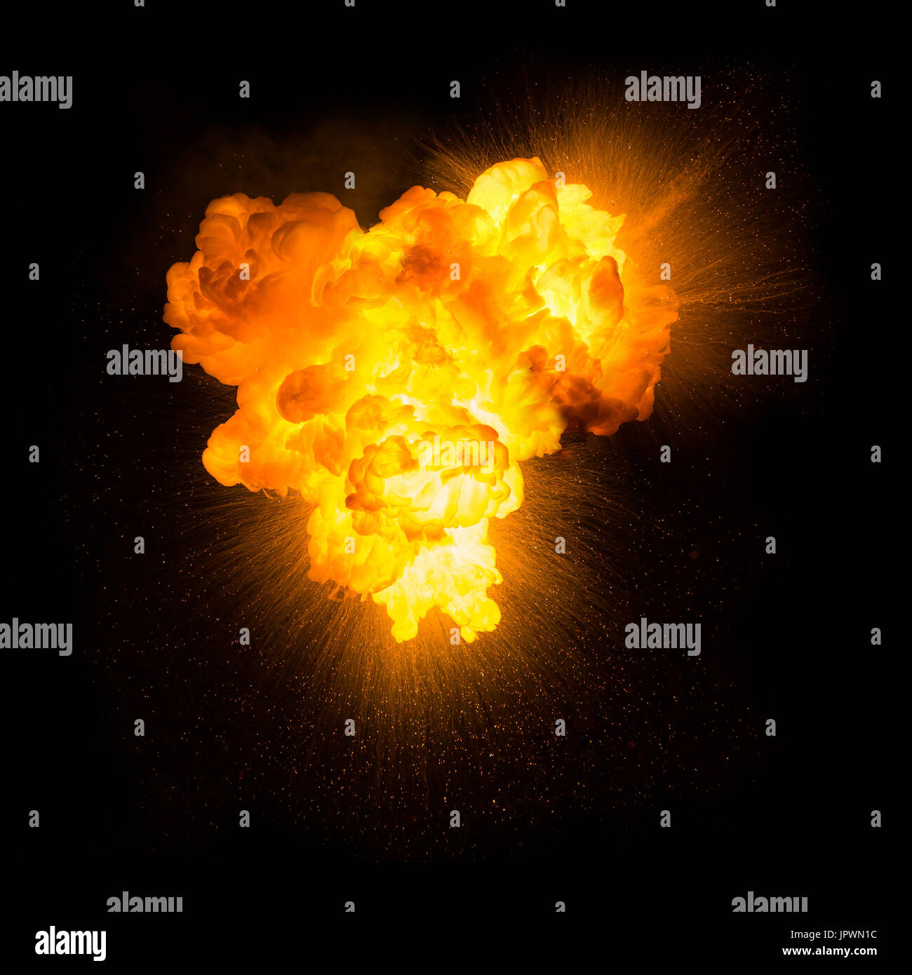 Realistic fiery explosion with sparks over a black background - Stock Image