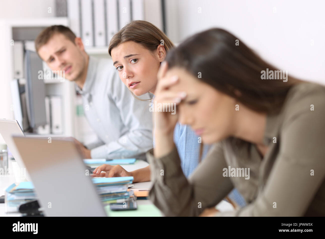 Sad workers looking at a frustrated colleague who is reading bad news on line at office - Stock Image