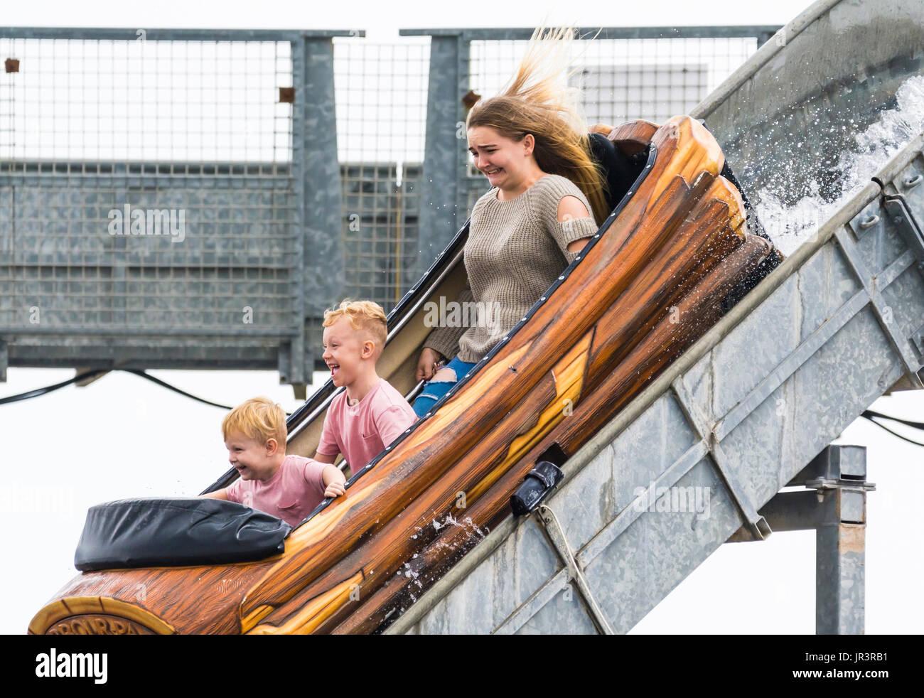 children-riding-on-a-long-flume-water-ride-in-summer-at-an-amusement-JR3RB1.jpg