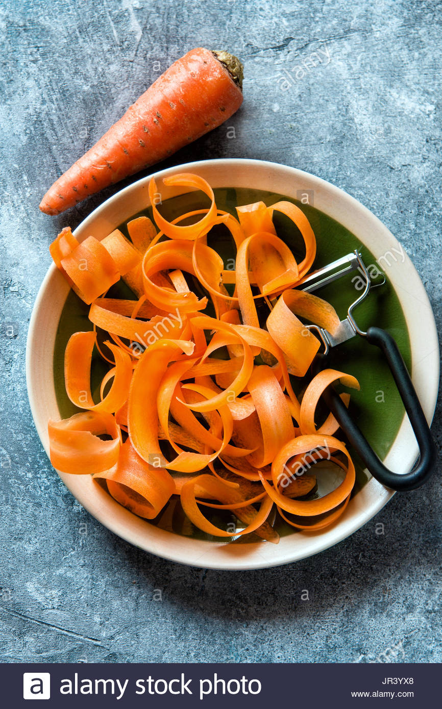Carrot shavings and a vegetable peeler on a plate.Top view - Stock Image