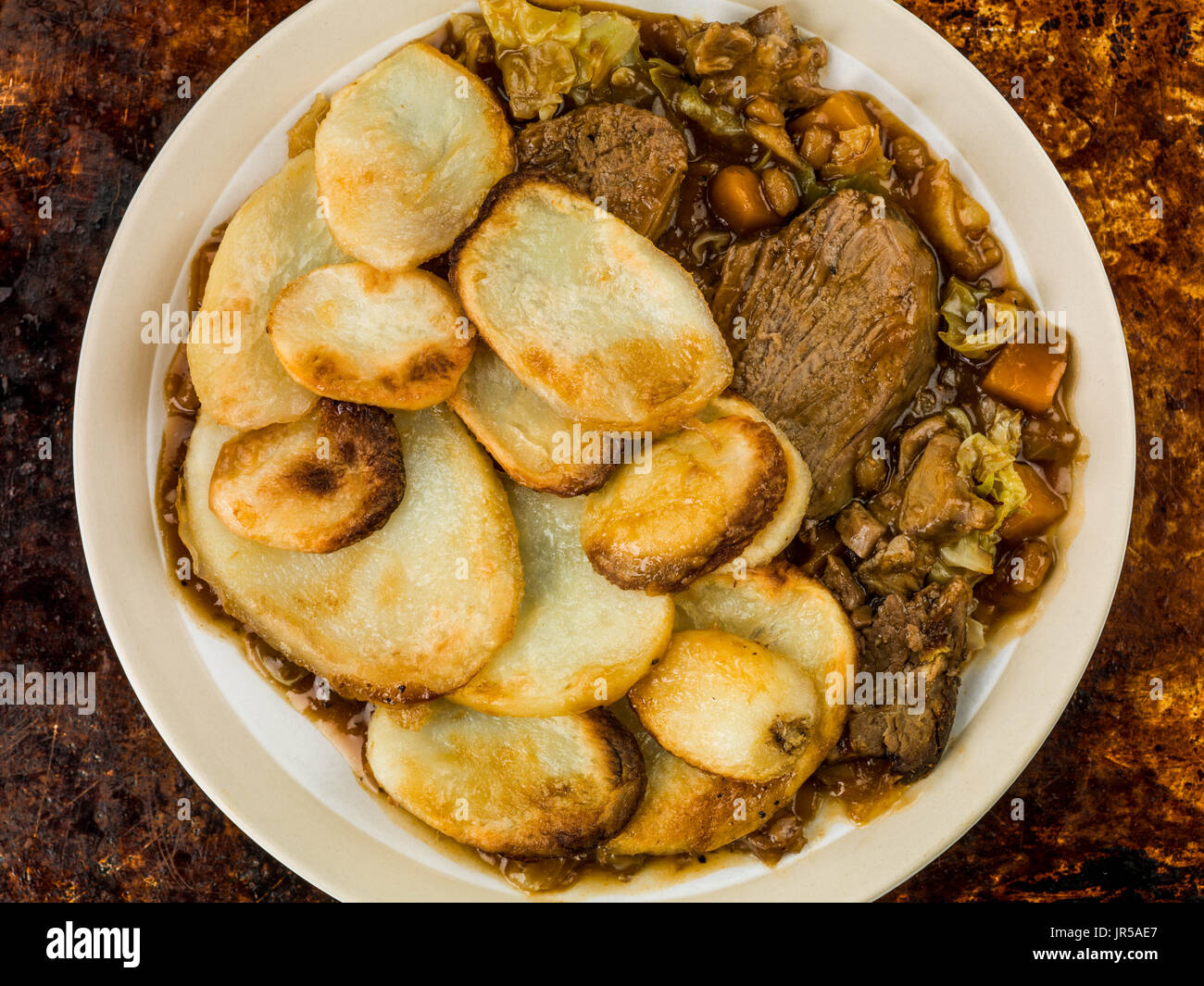 Lamb Hotpot With Sliced Potatoes and Onion Gravy Against a Distressed Burnt Oven or Baking Tray - Stock Image
