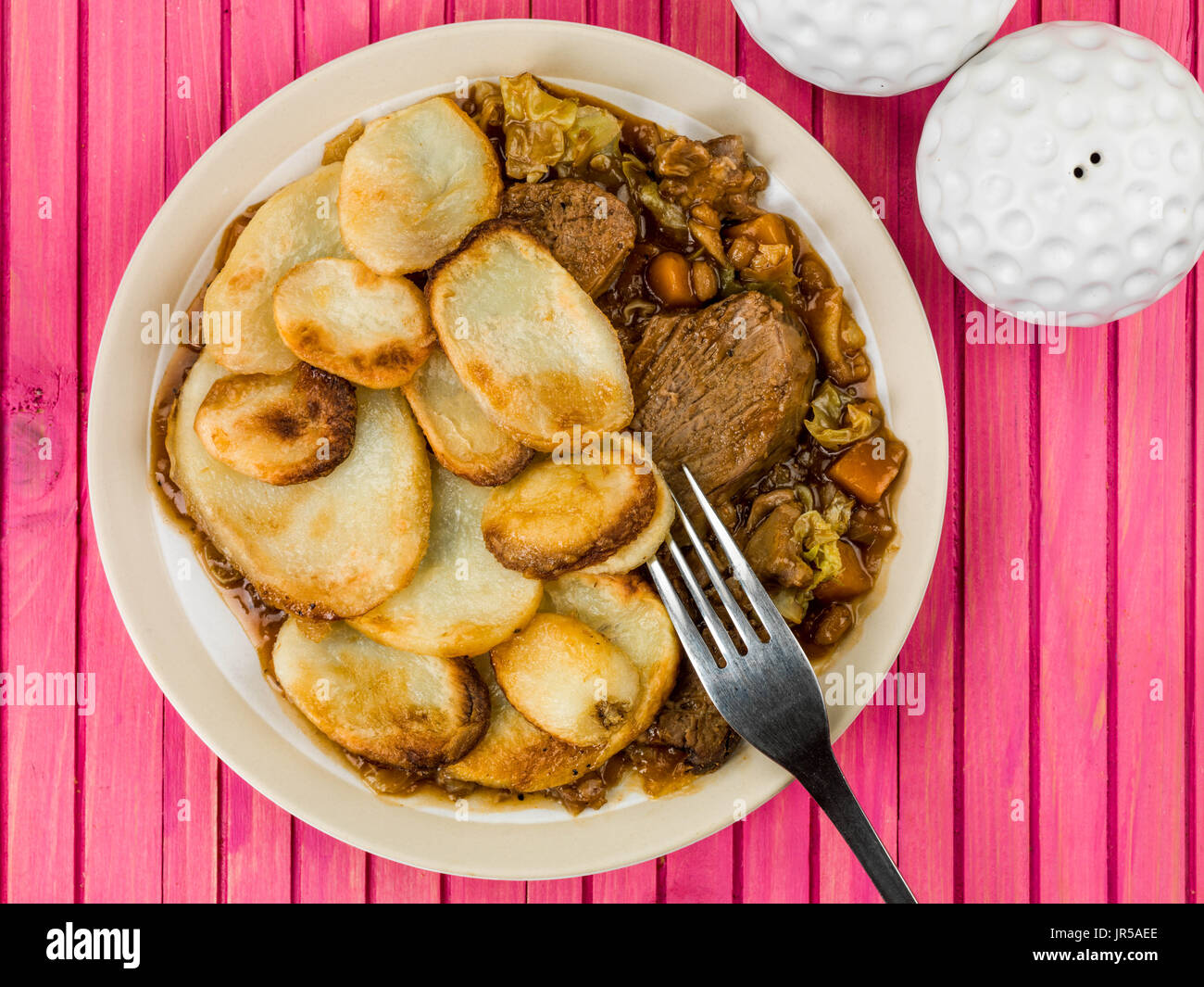 Lamb Hotpot With Sliced Potatoes and Onion Gravy Against a Pink Wooden Background - Stock Image