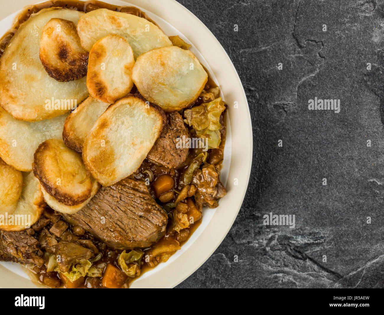 Lamb Hotpot With Sliced Potatoes and Onion Gravy Against a B;ack Slate Tile Background - Stock Image