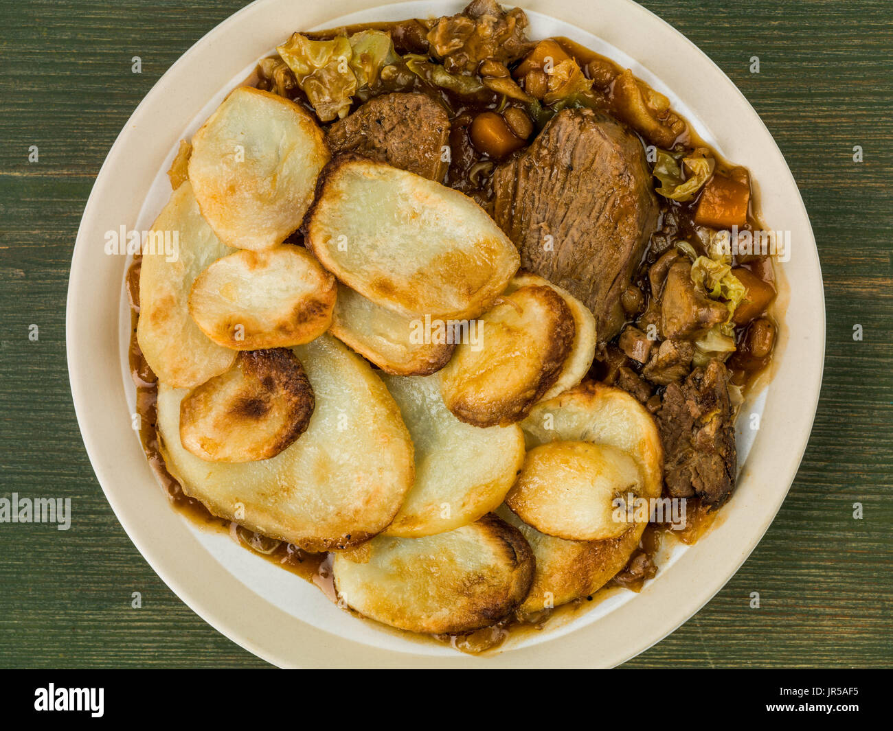 Lamb Hotpot With Sliced Potatoes and Onion Gravy Against a Green Wooden Background - Stock Image