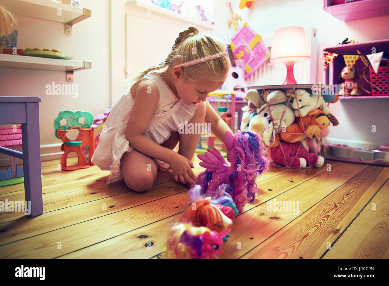 Thoughtful little girl putting toys in line on the floor. Horizontal indoors shot. - Stock Image