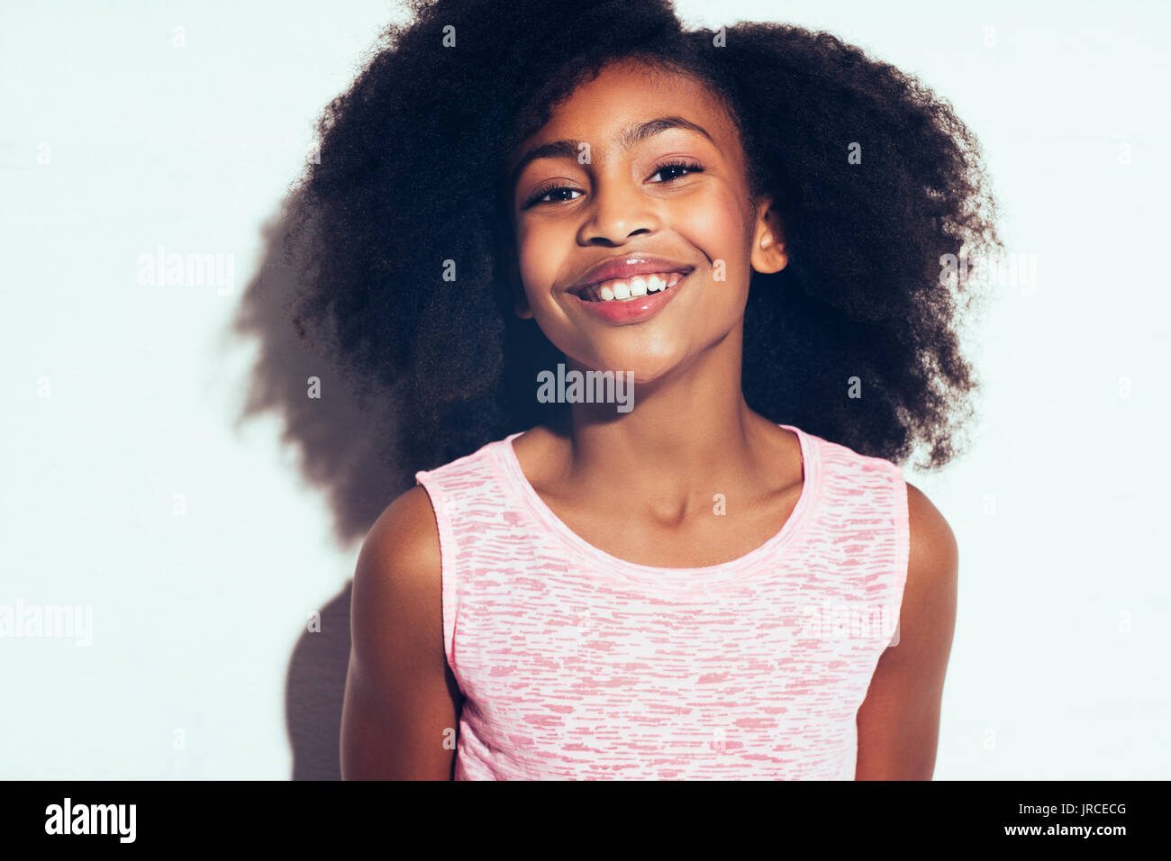 Cute young African girl with long curly hair smiling confidently while standing by herself against a gray background - Stock Image