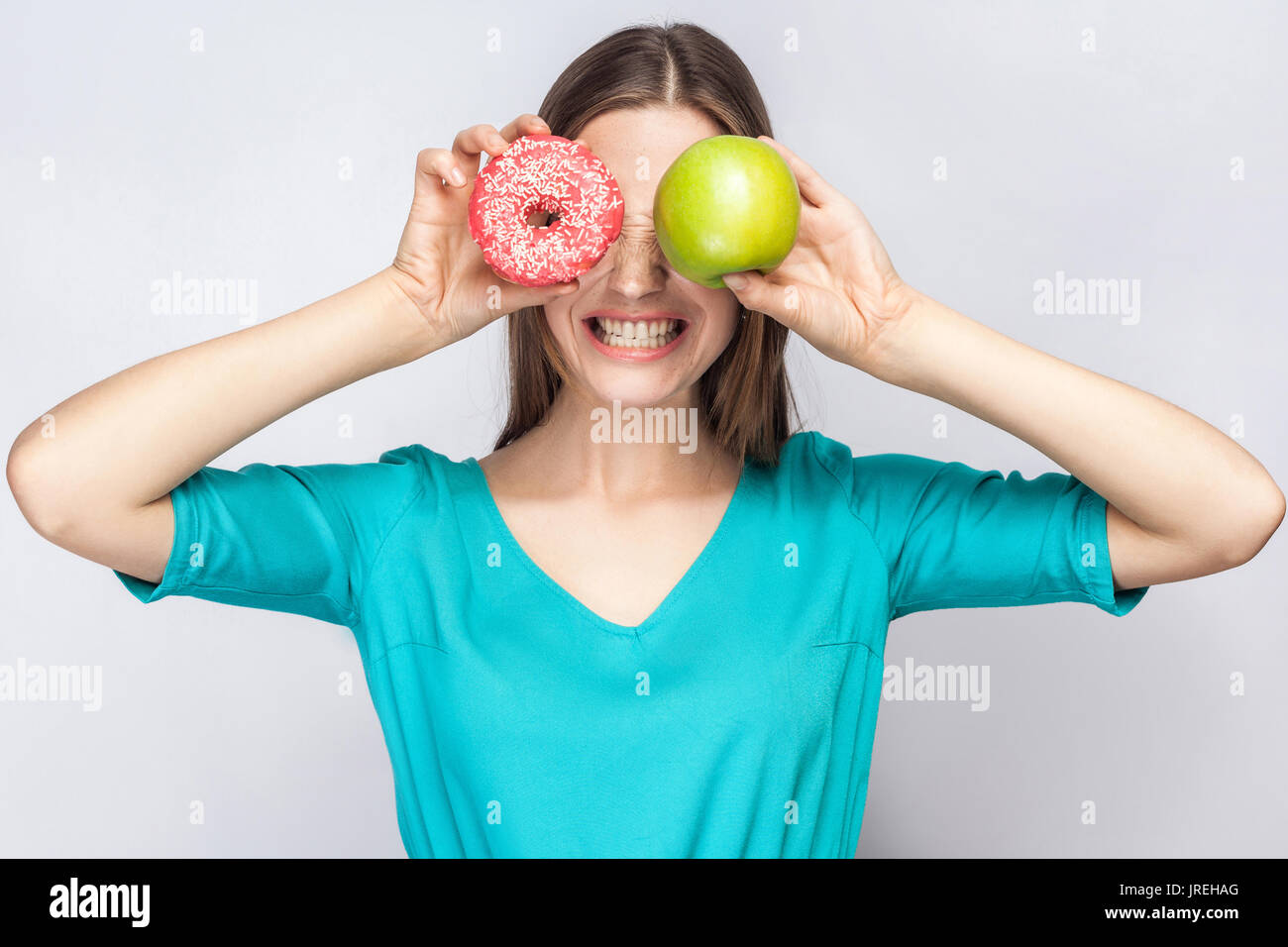 Beautiful young woman with freckles in green dress, holding before her eyes green apple and pink donut and shows - Stock Image