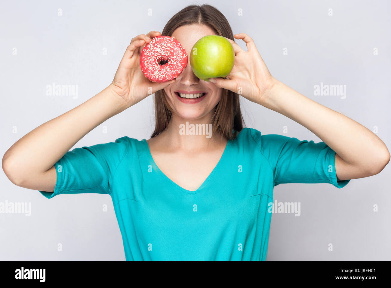 Beautiful young woman with freckles in green dress, holding before her eyes green apple and pink donut with toothy - Stock Image