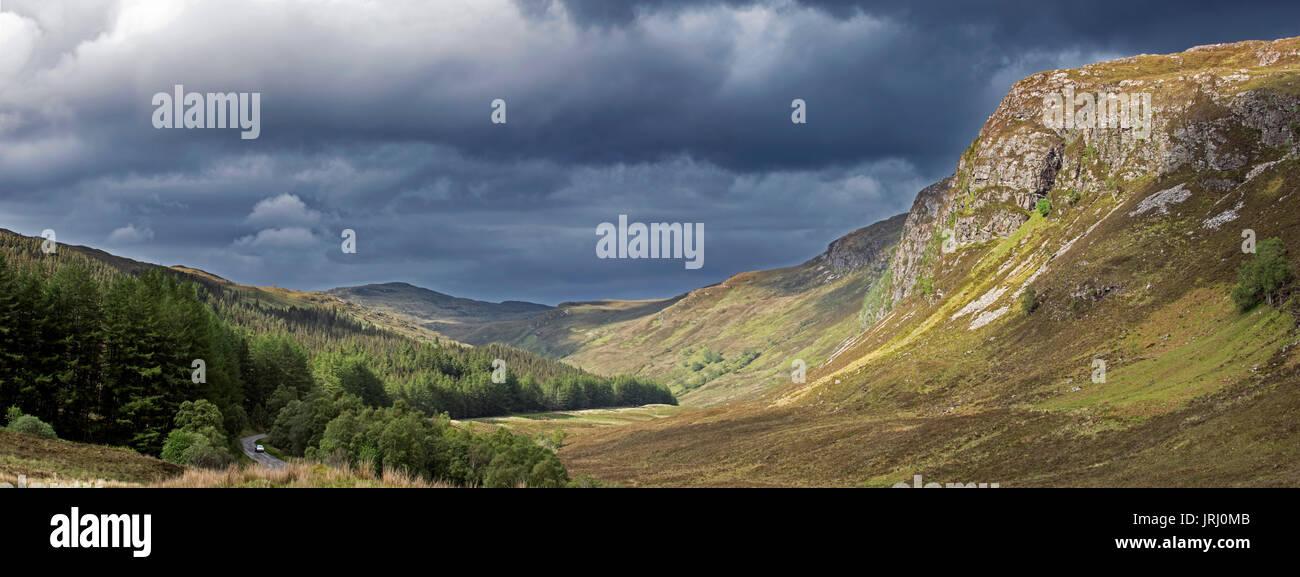 mountain-scenery-showing-dark-rain-clouds-rolling-in-over-sunny-hillside-JRJ0MB.jpg