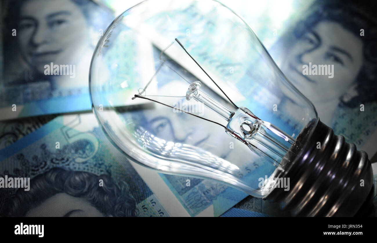 ELECTRIC LIGHT BULB WITH BRITISH MONEY RE ENERGY PRICES ELECTRICITY SUPPLIERS RISING FUEL COSTS HOUSEHOLD BUDGETS - Stock Image