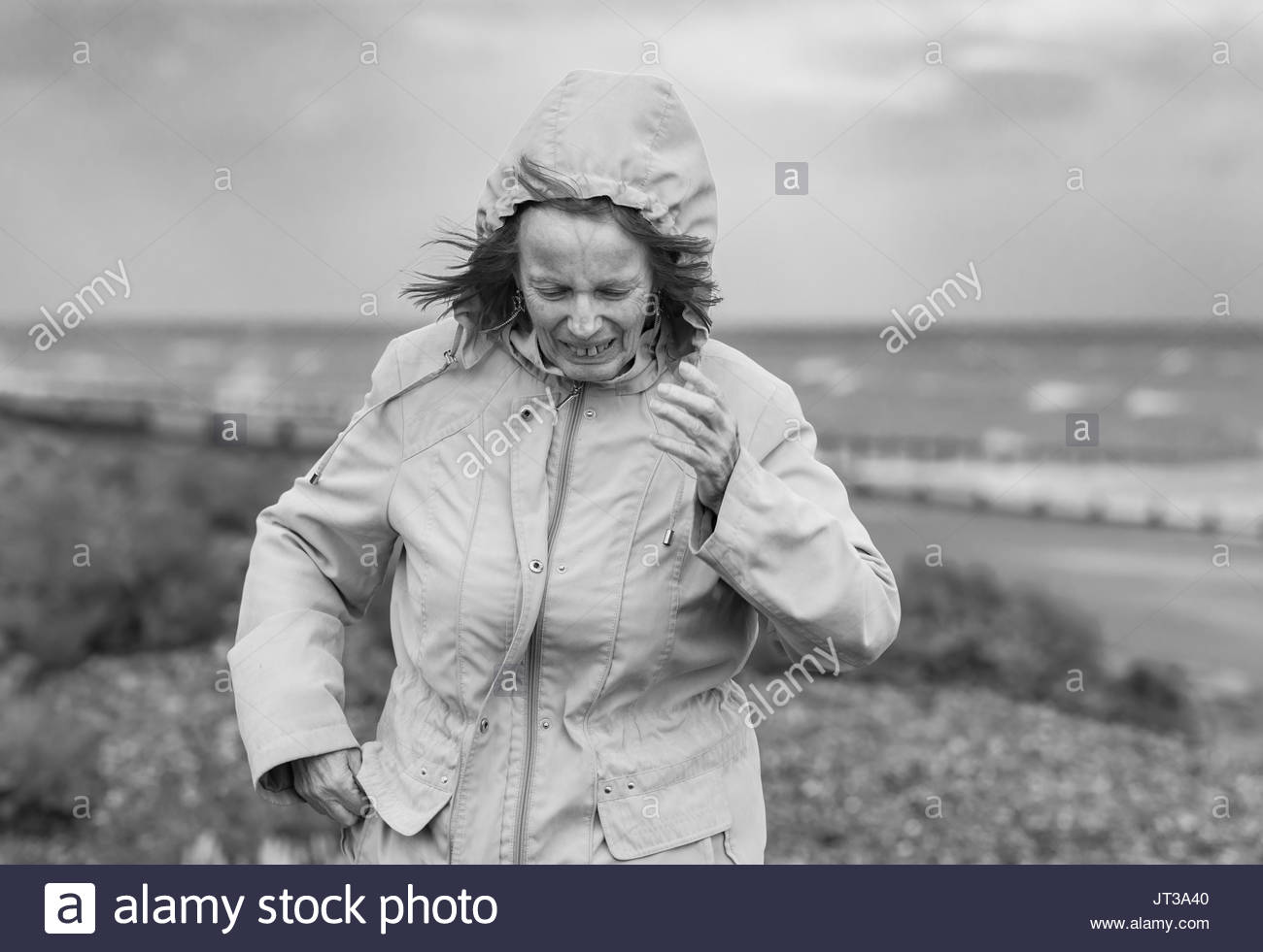 Elderly / Middle aged woman running to escape the poor weather on a beach on a cold windy day in the UK. Black & - Stock Image