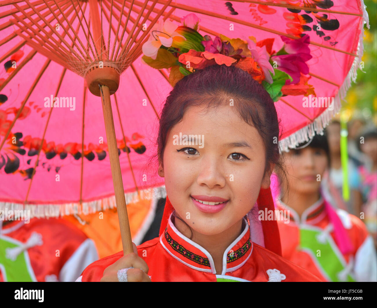 Smiling Thai Chinese Girl in Traditional Dress with Red Parasol (III), Northern Thailand. - Stock Image