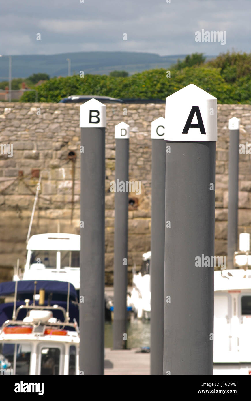 The lettered mooring posts supporting the jetty in the harbour in Porthcawl, Wales - Stock Image