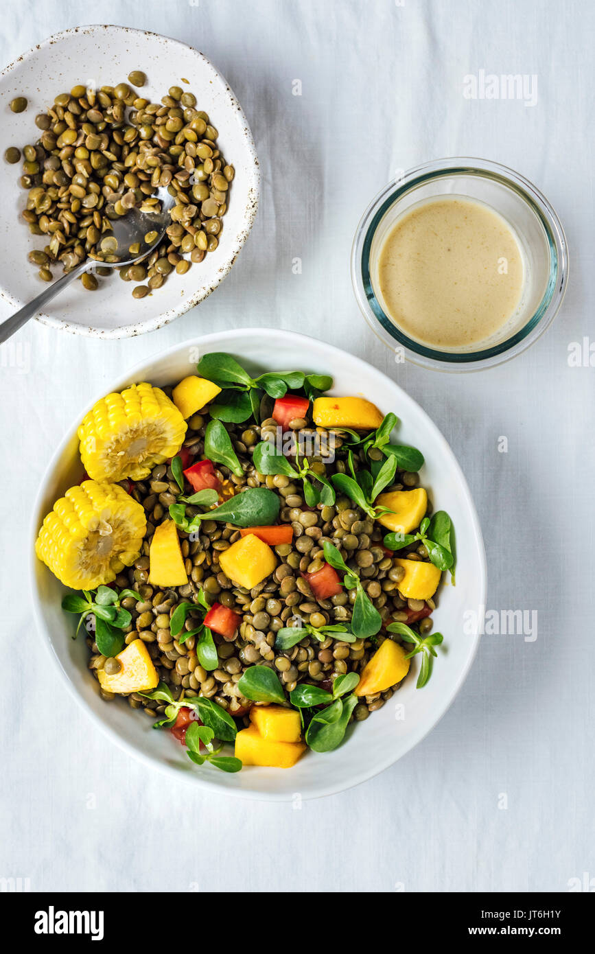 Lentil salad with herbs, tomatoes and peaches in a white bowl is photographed from top view. It is accompanied by - Stock Image