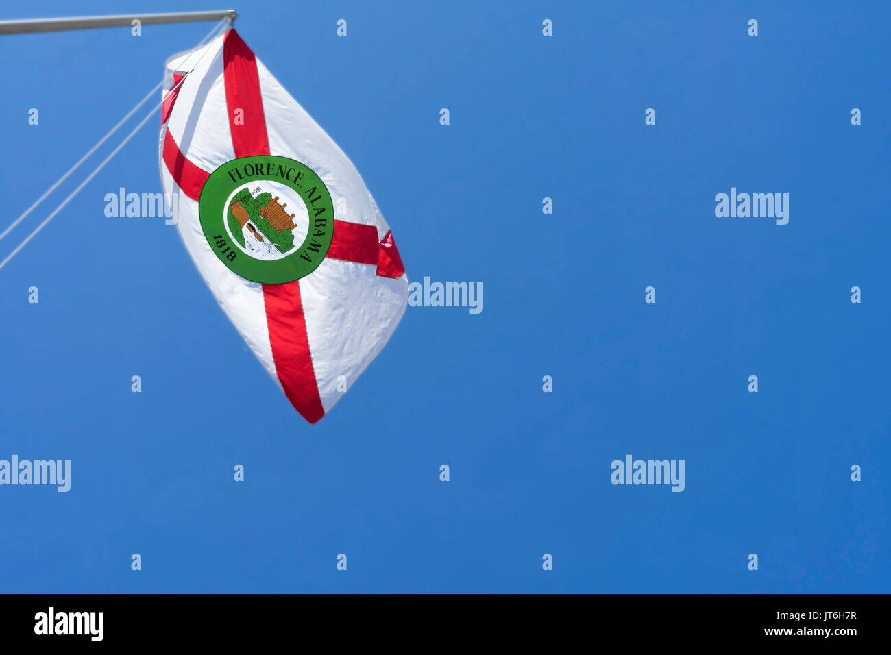 The flag of Florence, Alabama flutters in the breeze above the Tennessee River. - Stock Image