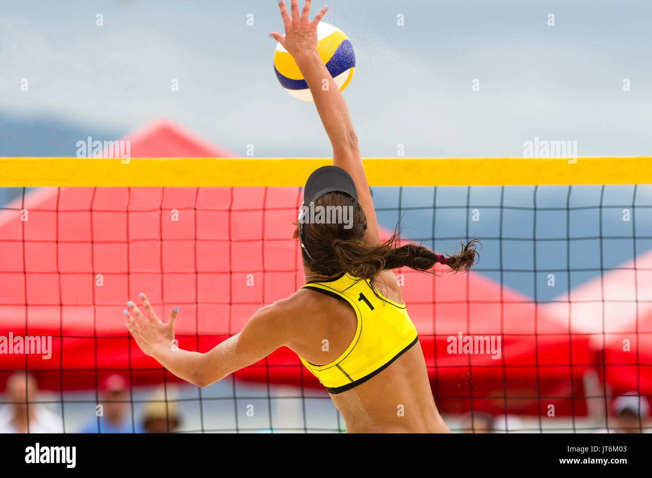 Volleyball player is a female beach volleyball player jumping at the net to spike the ball down. - Stock Image