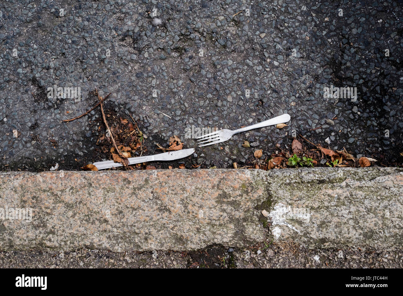 Knife and fork discarded in the road next to a kerb - Stock Image