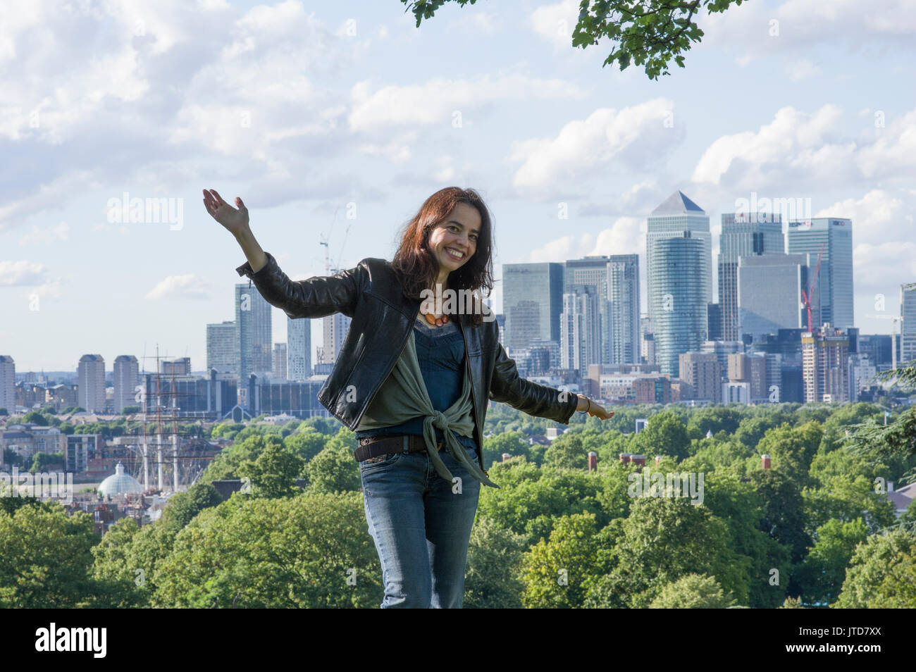 Woman stands in South London with The City of London and views of Canary Wharf in the background on a sunny day - Stock Image