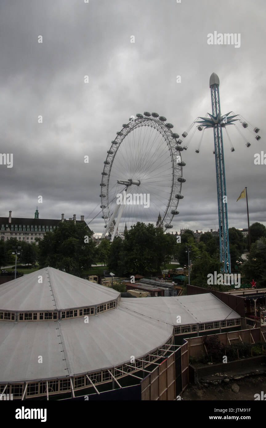 Overcast, cloudy day in London with a view of an amusement park ride and the London Eye ferris wheel against the - Stock Image