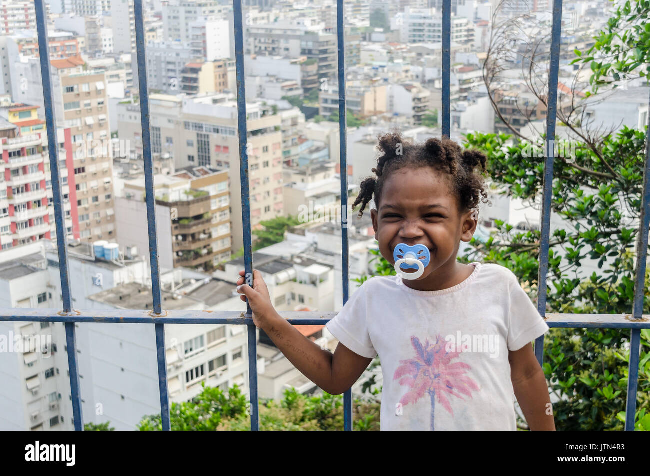 A girl (4-6) smiles with Ipanema, Rio de Janeiro background. A message written on a girl's arm that translates to Stock Photo