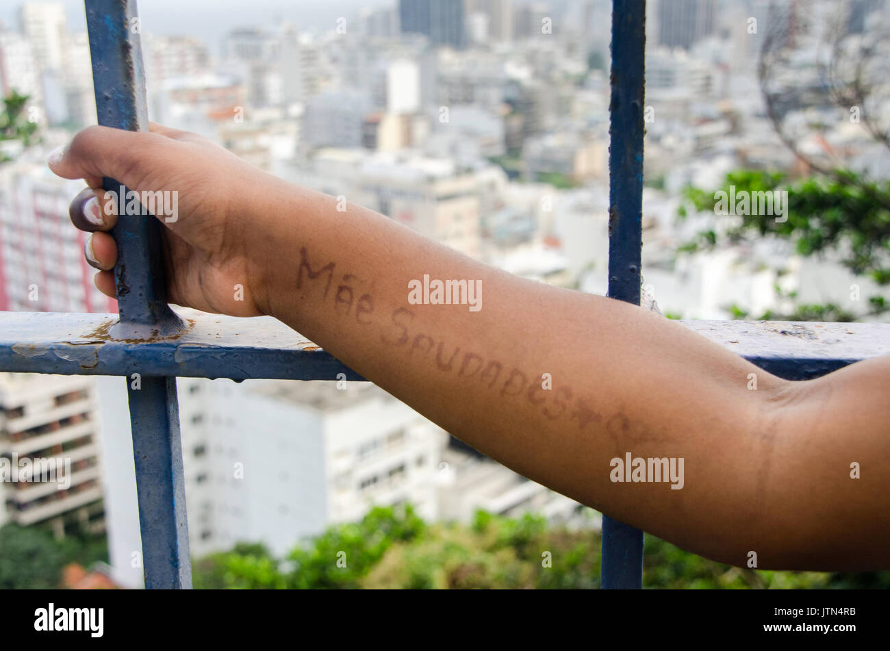"A message written on a girl's arm that translates to ""I miss you mom"". Taken at a favela in Rio Stock Photo"