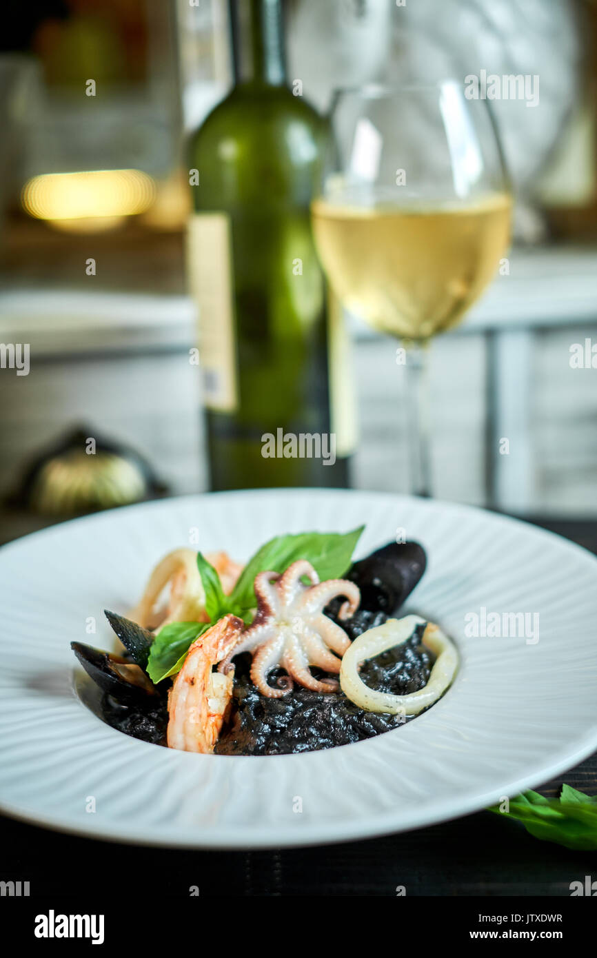Dish of risotto with squid ink on grey plate jpg - Stock Image