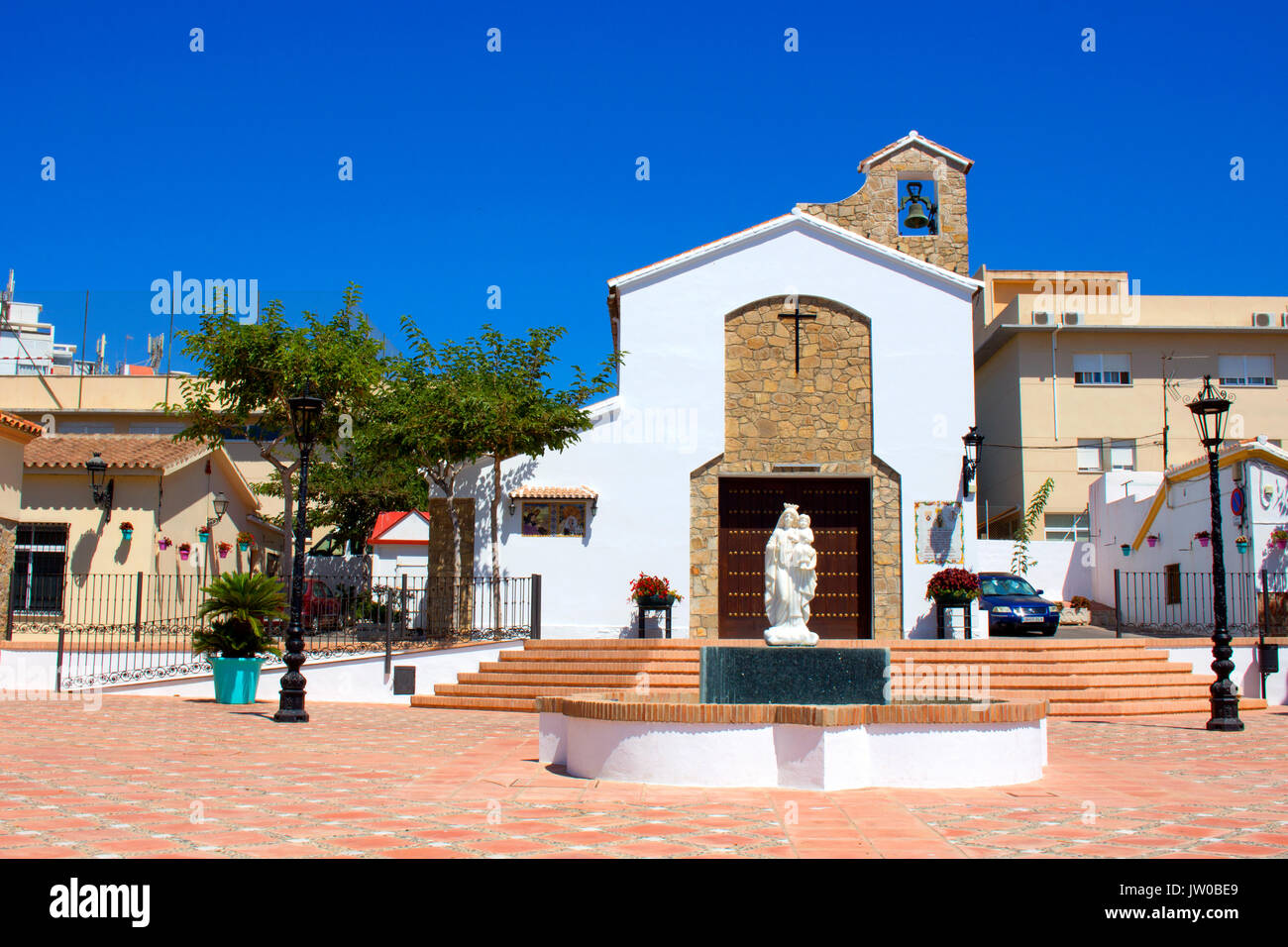 Church. Mother and child fountain in a town square with a church to the rear, Estepona, Malaga Province, Andalusia, - Stock Image