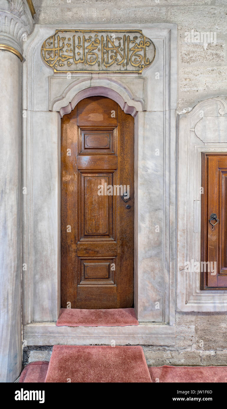 Wooden aged engraved door and marble wall, Eyup Sultan Mosque, Istanbul, Turkey - Stock Image