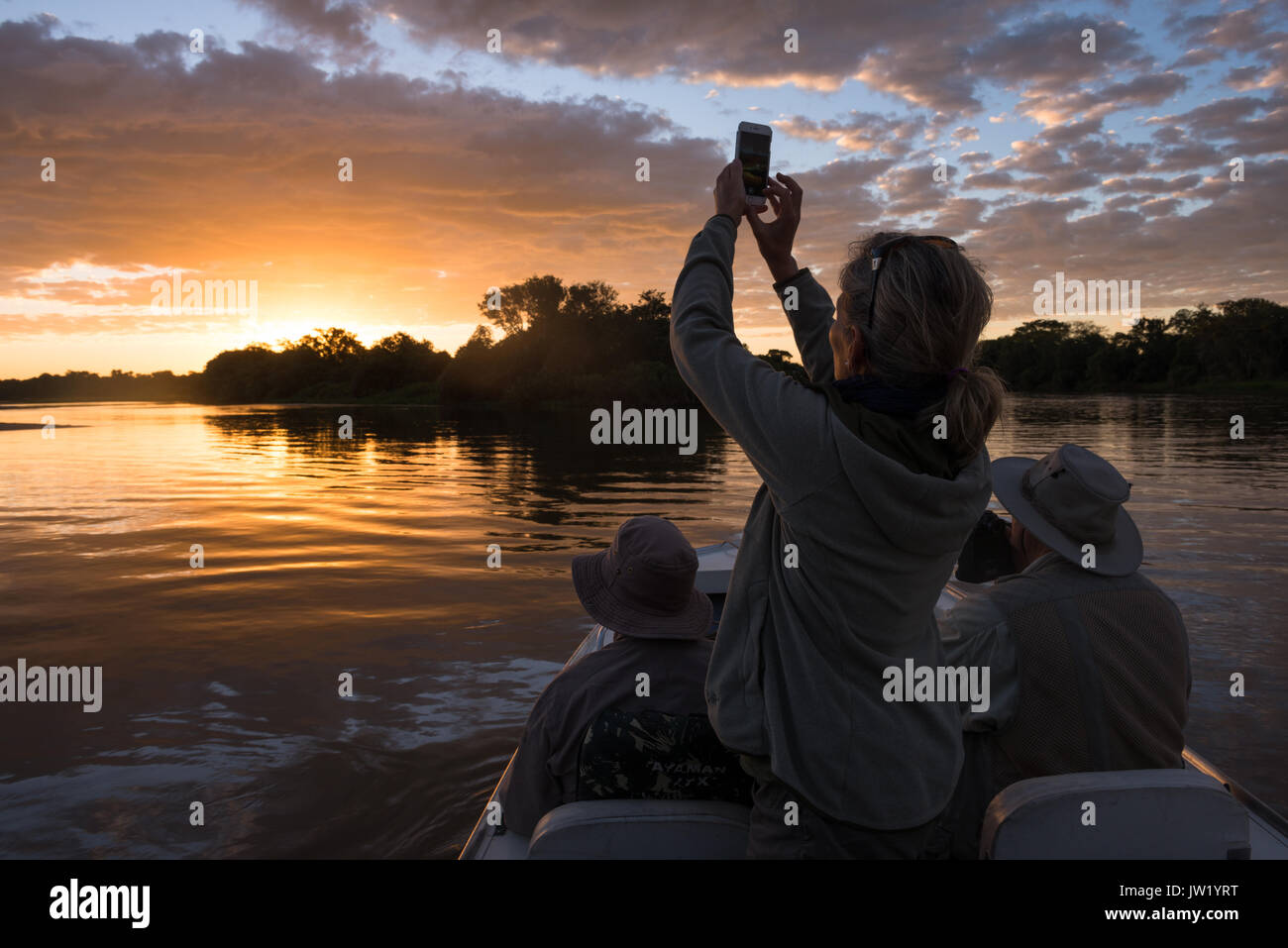 Tourist photographing the sunset with an iPhone Stock Photo