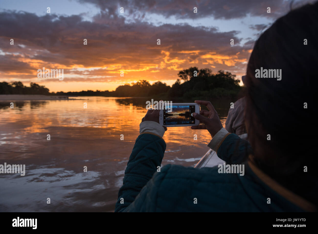 Tourist photographing the sunset with an iPhone - Stock Image