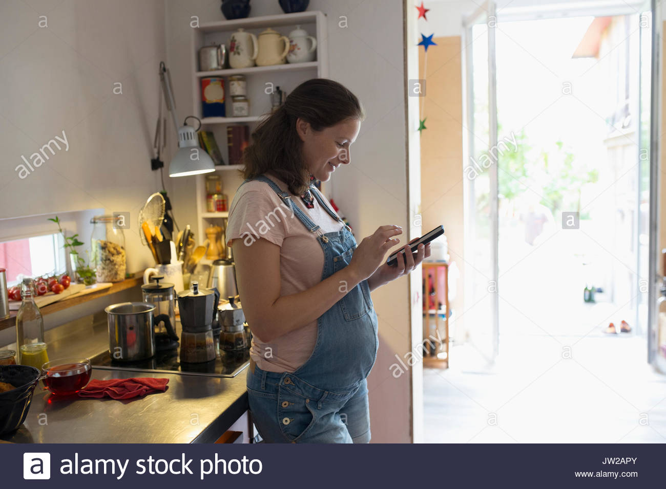 Pregnant woman using cell phone in kitchen - Stock Image