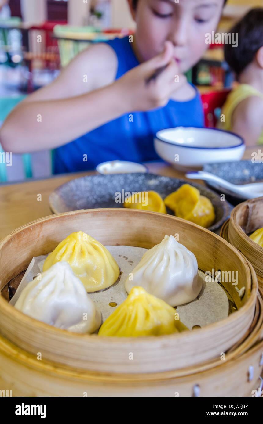 a-young-boy-eats-chinese-soup-dumplings-in-shanghai-JWFJ3P.jpg