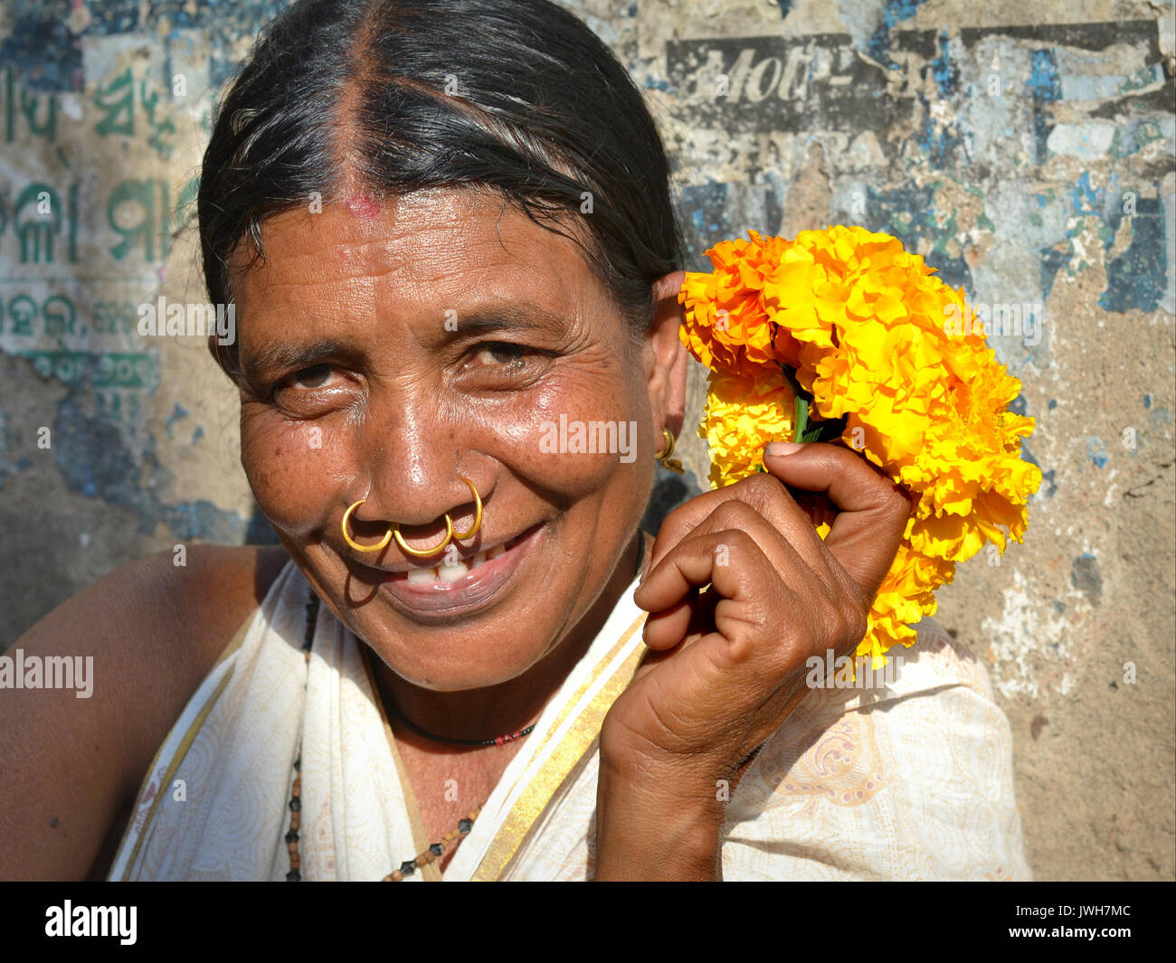 Closeup street portrait (outdoor headshot, seven-eighths view) of a smiling mature Indian Adivasi flower seller Stock Photo