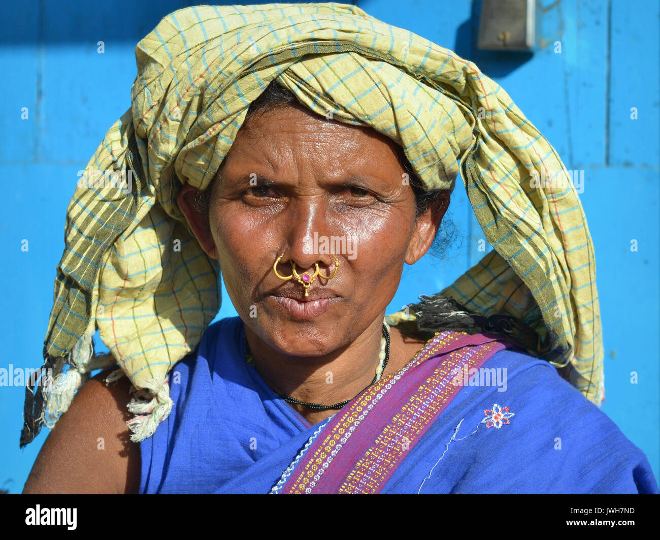 Closeup street portrait (outdoor headshot, full-face view) of a mature Indian Adivasi market woman with two golden - Stock Image