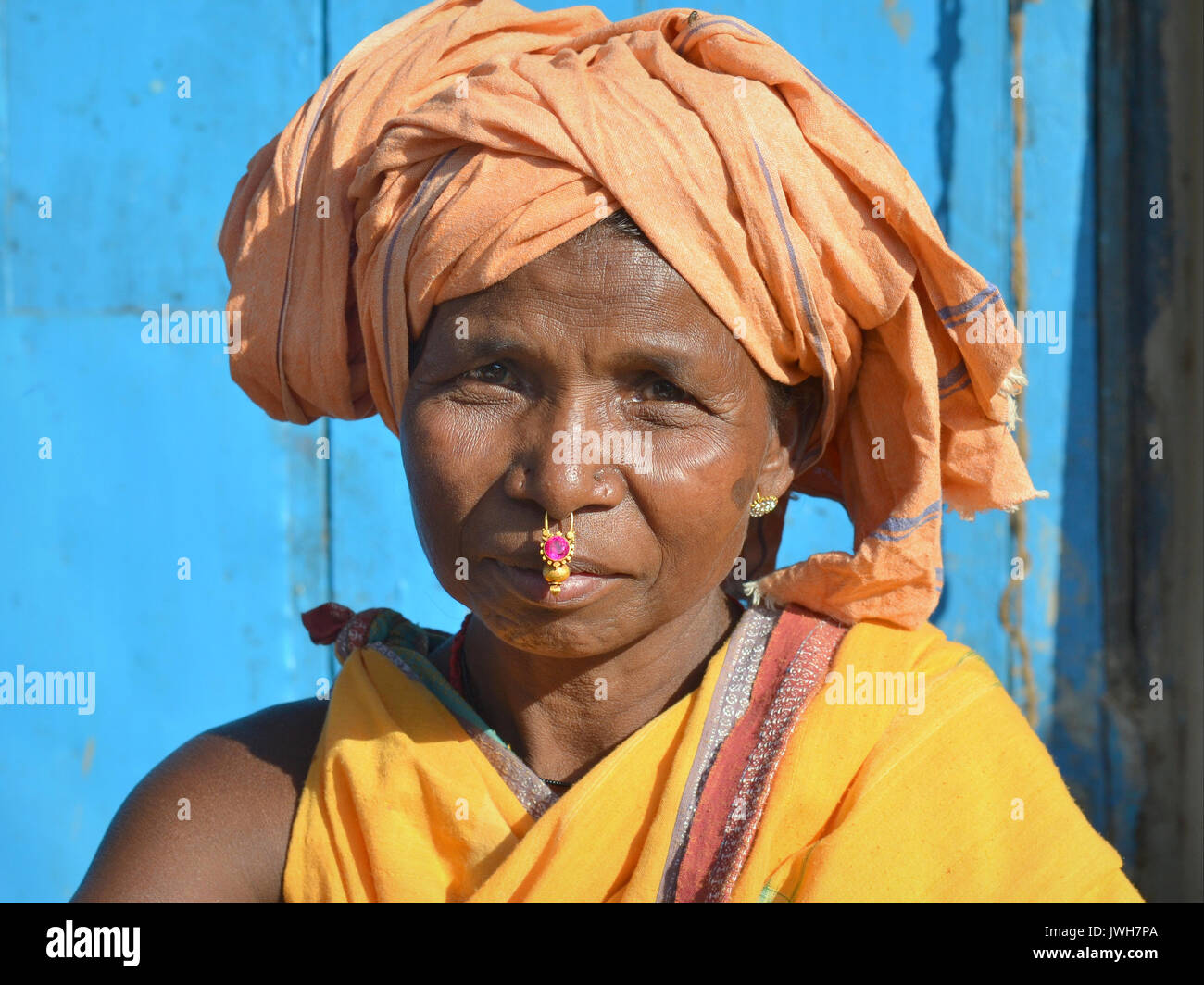Closeup street portrait (outdoor headshot, seven-eighths view) of a mature Indian Adivasi market woman with gold Stock Photo