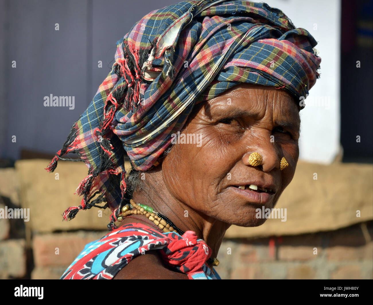 Closeup street portrait (outdoor headshot, three-quarter view) of an elderly Indian Adivasi market woman with two - Stock Image