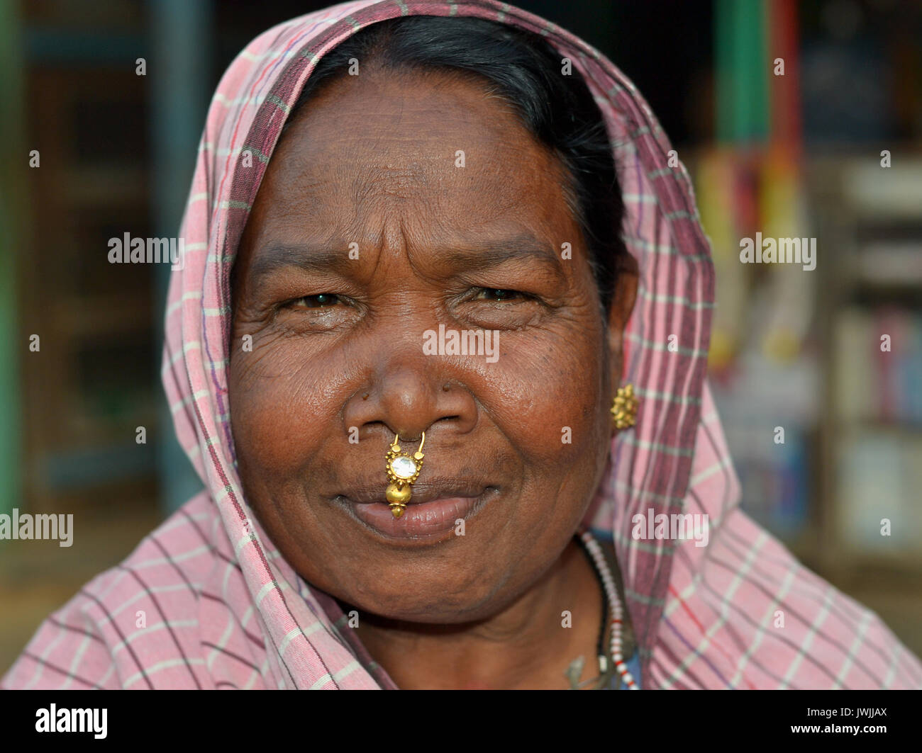 Closeup street portrait (outdoor headshot, seven-eighths view) of an overweight, mature Indian Adivasi market woman Stock Photo