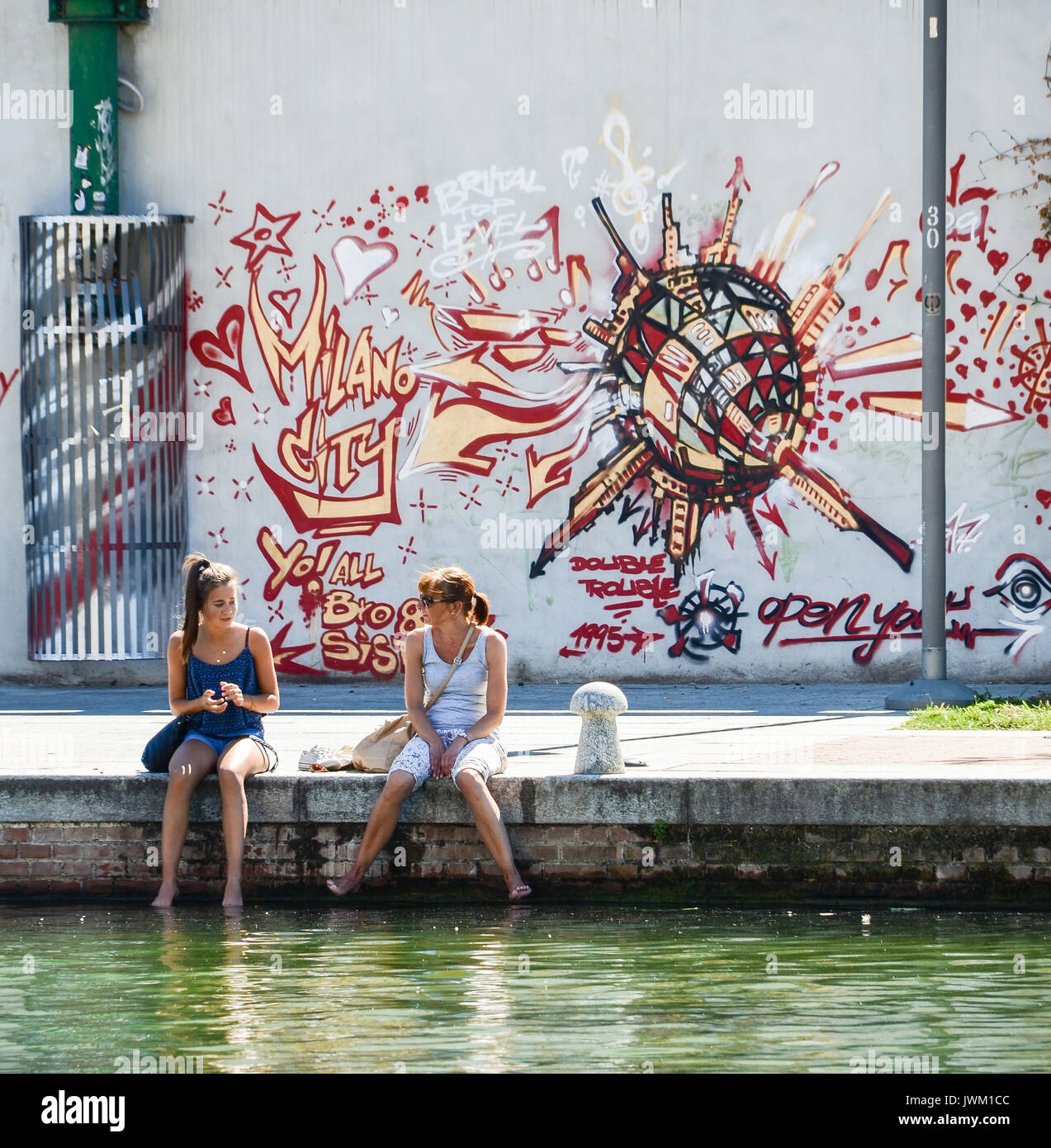 Mother and daughter on the canal in Bohemian Navigli, Milan, Italy Stock Photo