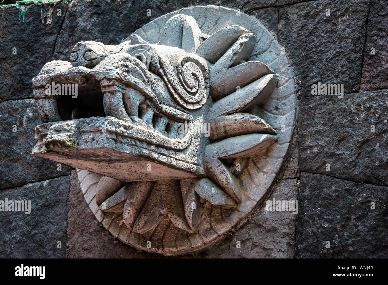 Old stone carving of quetzalcoatl the ancient feathered
