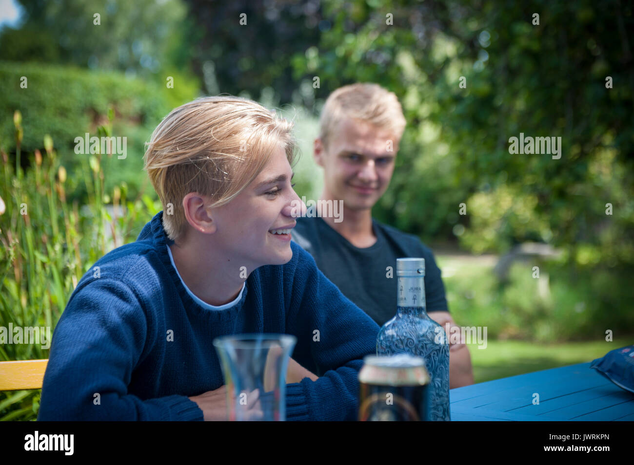 Two blonde brothers having a drink in the garden - Stock Image