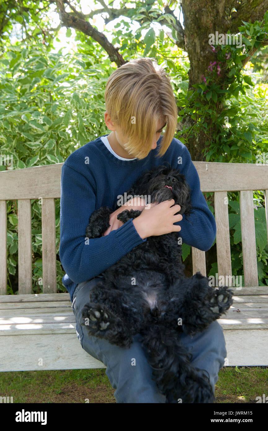 A blonde teenaged boy hugs his black dog - Stock Image