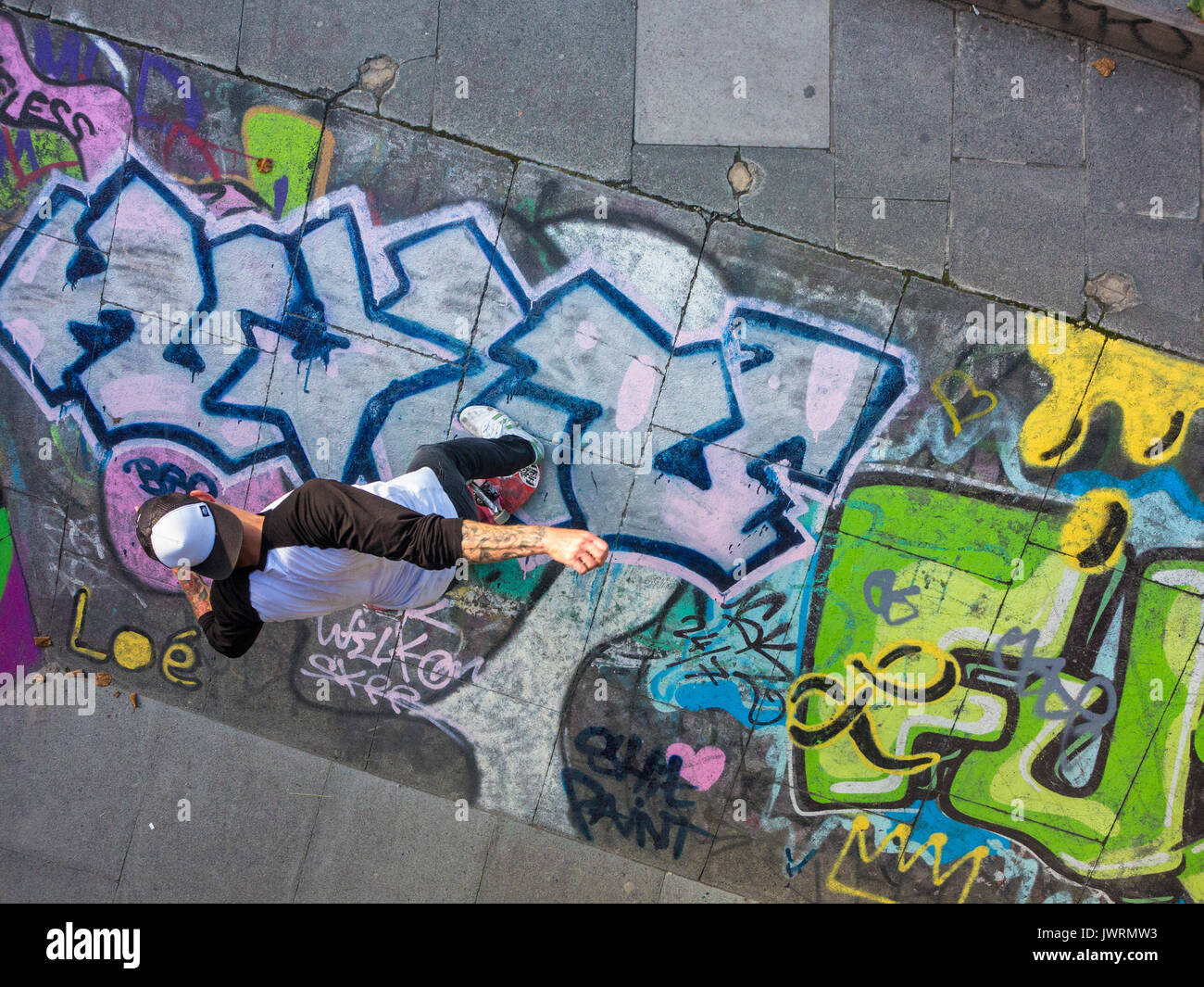 A skateboarder performs a trick, shot from above as an unusual angle - Stock Image